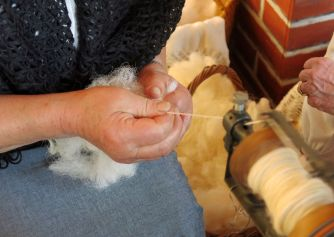 33041008 - elderly woman works the wool with an antique spinning wheel